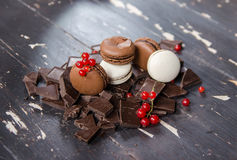 Chocolate and white macarons over pieces of chocolate on wooden background. Close up. Stock Images