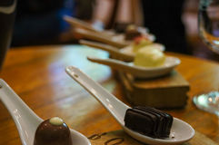 Chocolate in white spoons for testing wine. Stock Image