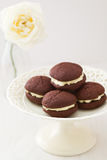 Chocolate whoopie pies on cake stand Stock Photos