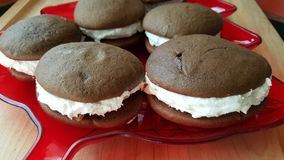 Chocolate Whoopie Pies. Chocolae Whoopie Pies on a red Christmas tree tray on cutting board royalty free stock photography