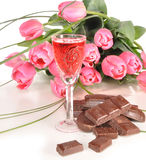 Chocolate, wine and tulips. Chocolate, wine-glass of wine and bouquet of tulips lie on a table Stock Photography