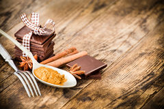 Chocolate wood table surrounded by spices. Royalty Free Stock Image