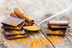 Chocolate wood table surrounded by spices. Royalty Free Stock Photography