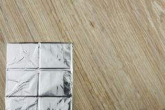 Chocolate wrapped in aluminum foil on a wooden board. Stock Image