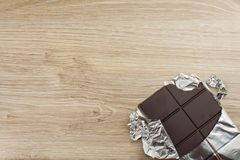 Chocolate wrapped in aluminum foil on a wooden board. Royalty Free Stock Photography