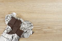 Chocolate wrapped in aluminum foil on a wooden board. Royalty Free Stock Photo