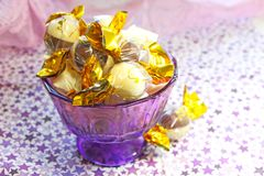 Chocolate wrapped in a gold wrapper in a purple jar. Chocolate wrapped in a gold wrapper in a purple small jar on a napkin printed with stars Stock Photos