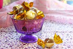 Chocolate wrapped in a gold wrapper in a purple jar. Chocolate wrapped in a gold wrapper in a purple small jar on a napkin printed with stars Royalty Free Stock Photography