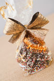 Chocolate wreath decorated with sprinkles and bow, wrapped in plastic foil Stock Photography