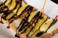 Chocolate y mantequilla en el pan tostado Fotos de archivo libres de regalías