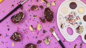 Chocolate y pedazos de mentira en un fondo brillante, caramelo brillante del chocolate Chocolate blanco y negro