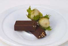 Chocolate y tuercas en una meseta Fotografía de archivo