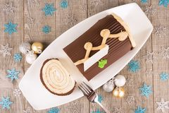 Chocolate yule log cake with Christmas decorations disposed on wooden table. stock photography