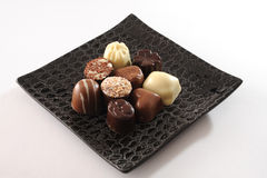 Chocolates. Selection of delicious hand made luxury chocolates on black plate royalty free stock images