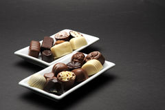 Chocolates. Selection of delicious hand made luxury chocolates on white plates royalty free stock photo