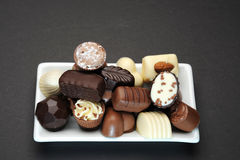 Chocolates. Selection of delicious hand made luxury chocolates on a white plate royalty free stock image