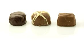 Chocolates. Three filled chocolates in a row isolated on white studio background Royalty Free Stock Image