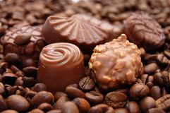 Chocolates against coffee grains Stock Photos