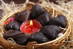 Chocolates alrededor de la vela en cesta del metal Fotografía de archivo libre de regalías