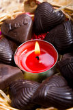 Chocolates around candle in metal basket Stock Photos