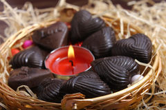 Chocolates around candle in metal basket Royalty Free Stock Photography