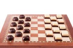 Chocolates blancos y negros en el tablero de ajedrez Fotografía de archivo libre de regalías