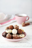 Chocolates in bowl on the white wooden background Stock Images
