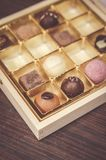 Chocolates in a box. Mix of chocolate bonbons in a wooden open box Stock Image