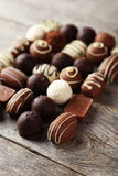 Chocolates on a brown wooden background Stock Photos