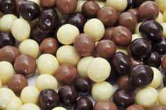 Chocolates. Closeup of some different ball-shaped chocolates made with black chocolate, white chocolate and milk chocolate royalty free stock photo