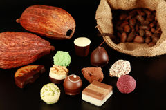 Chocolates, cocoa pods and beans. Various chocolate truffles, cocoa pods and cocoa beans in a sack Royalty Free Stock Photography