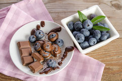 Chocolates and cocoa powder with blueberries in a porcelain dish Stock Photos