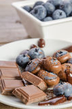 Chocolates and cocoa powder with blueberries in a porcelain dish Stock Photography