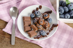 Chocolates and cocoa powder with blueberries in a porcelain dish Stock Image