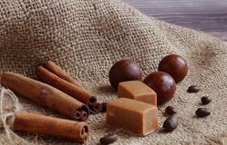 Close-up view of cinnamon sticks tied with string, chocolates and coffee beans are lying on a napkin on the table. Chocolates, coffee and cinnamon sticks on a stock photo