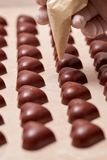 chocolates Coração-dados forma que estão sendo decorados com uma mão gloved imagens de stock