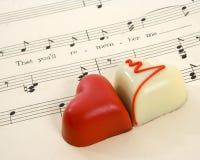 Chocolates del corazón del amor en música de hoja Imágenes de archivo libres de regalías