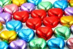 Chocolates del corazón envueltos en hoja colorida Fotografía de archivo