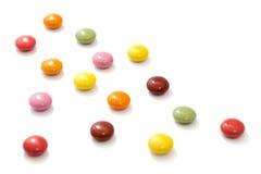 Chocolates dispersados coloridos isolados no fundo branco Fotografia de Stock Royalty Free