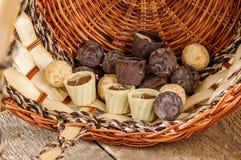 Chocolates e chocolate em uma cesta Fotos de Stock