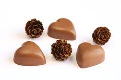 Chocolates e cones dados forma coração do pinho Imagens de Stock Royalty Free
