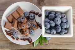 Chocolates e pó de cacau com mirtilos em um prato de porcelana fotografia de stock royalty free