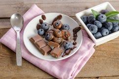 Chocolates e pó de cacau com mirtilos em um prato de porcelana foto de stock