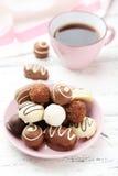 Chocolates en cuenco en el fondo de madera blanco Imagenes de archivo