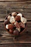Chocolates en cuenco en el fondo de madera marrón Foto de archivo