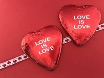 Chocolates en forma de corazón en fondo rojo foto de archivo