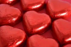Chocolates en forma de corazón en fondo rojo imagen de archivo