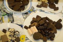 Chocolates en la placa en fondo negro imagen de archivo