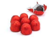 Chocolates envolvidos no vermelho Fotos de Stock Royalty Free