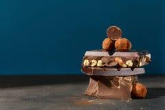 Chocolates escuros da pilha e da trufa do chocolate no fundo azul Foto de Stock Royalty Free